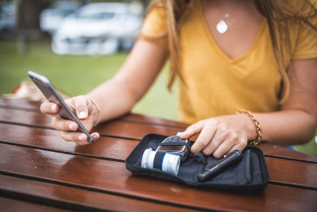woman checking out her phone while holding blood sugar control kit