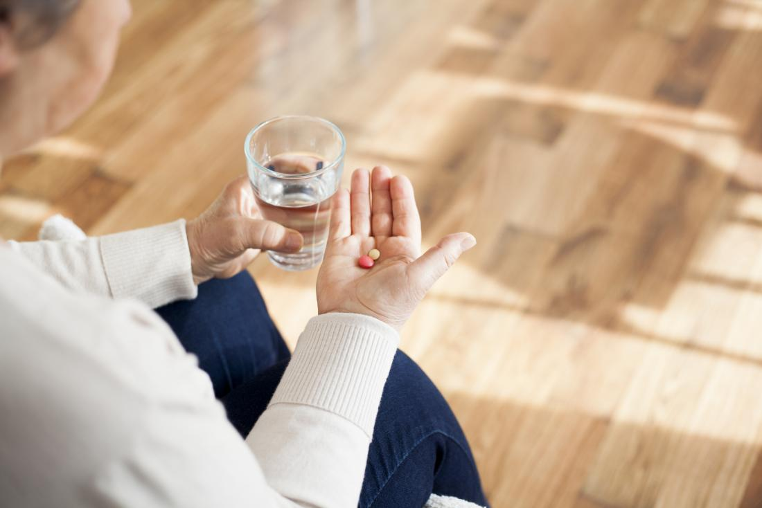 senior holding pills in one hand and a glass of water in the other