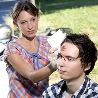 A woman helps a man with a head injury from crashing his bike.