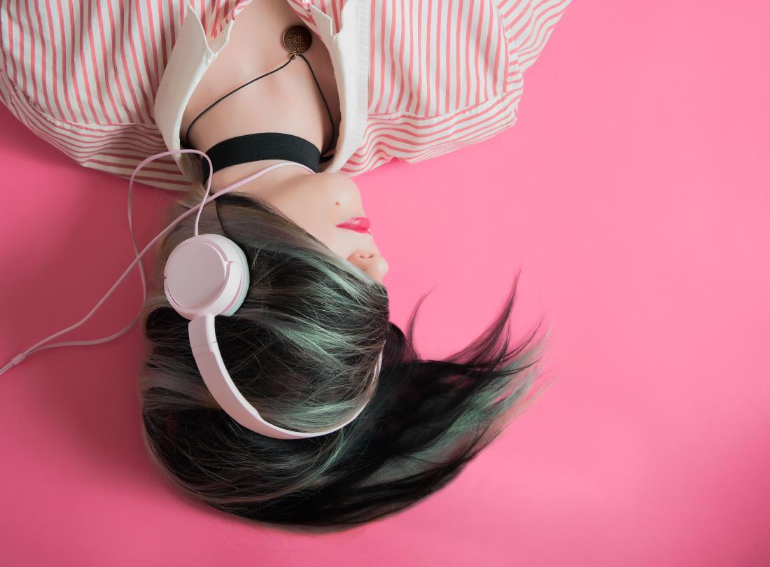 person listening to music through headphones