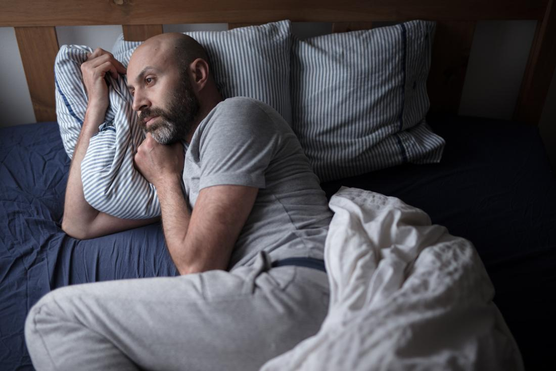 man with insomnia lying in bed