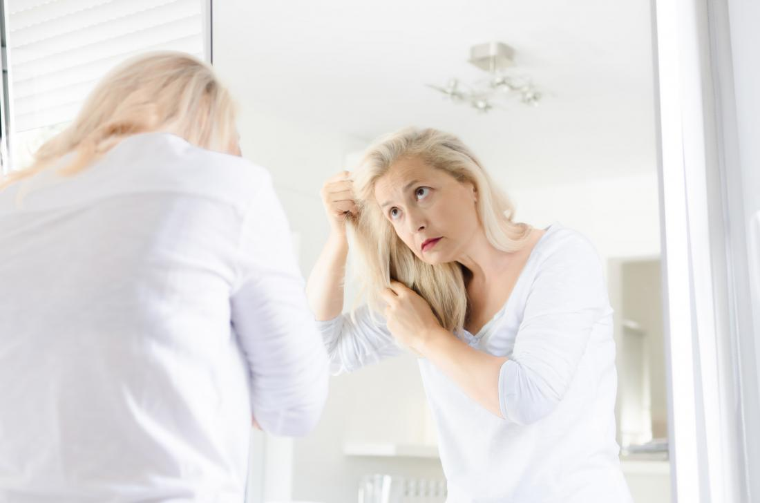 Woman touching hair due to adderall hair loss