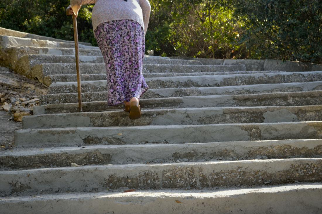 woman going up the stairs using walking stick
