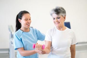 therapist helping woman to exercise arm