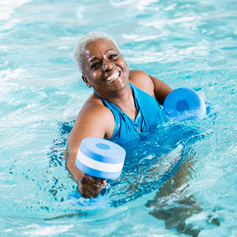 A woman performs water exercises in the pool to help with sacroiliac (SI) joint pain.