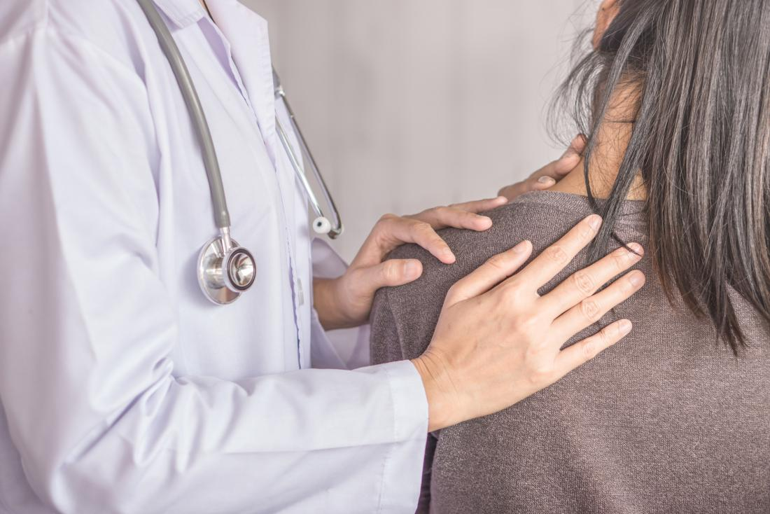 woman experiencing neck pain seen from the back
