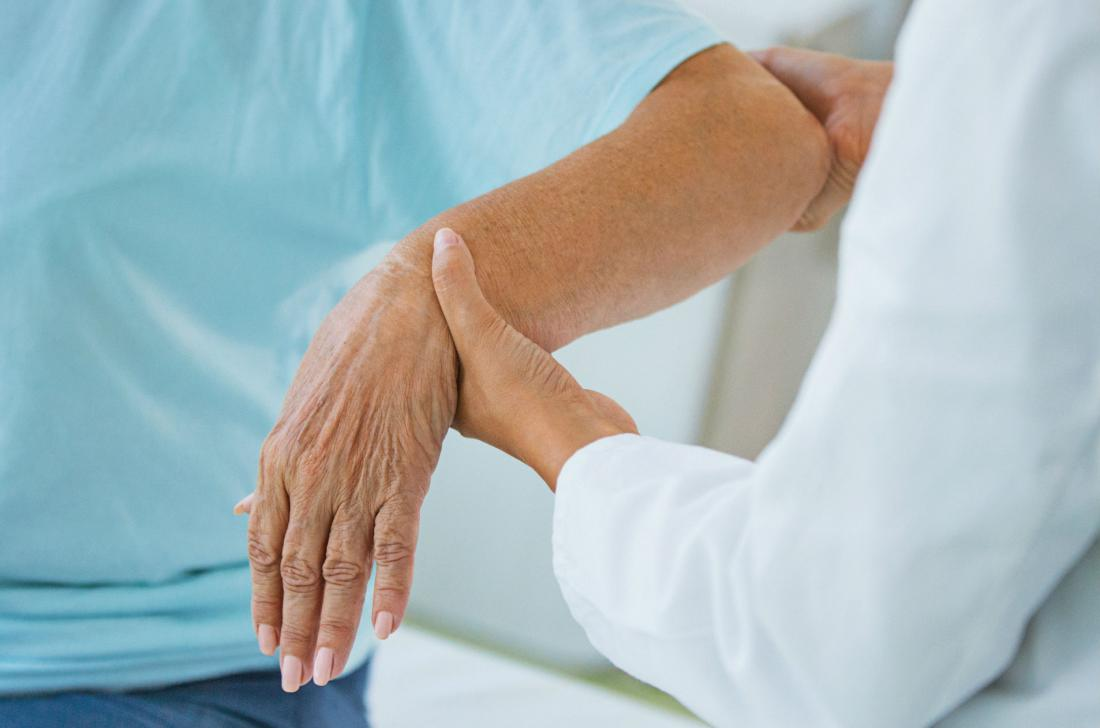close up of a healthcare professional checking a senior woman's hand for signs of arthritis