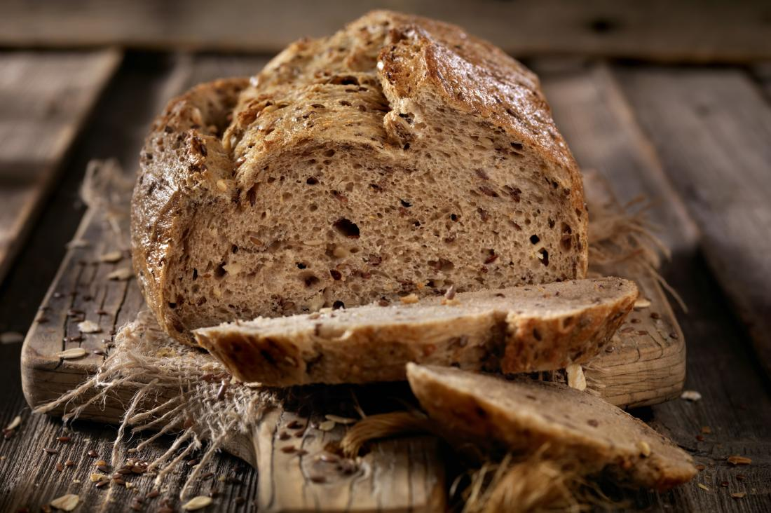 Whole grain artisan bread on chopping board.