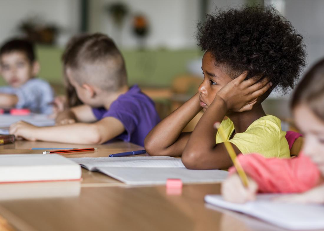 Child in school covering ears looking worried and upset struggling to work or study.