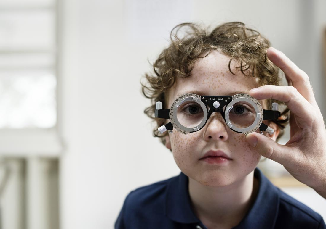 Child having eye exam check at opticians.