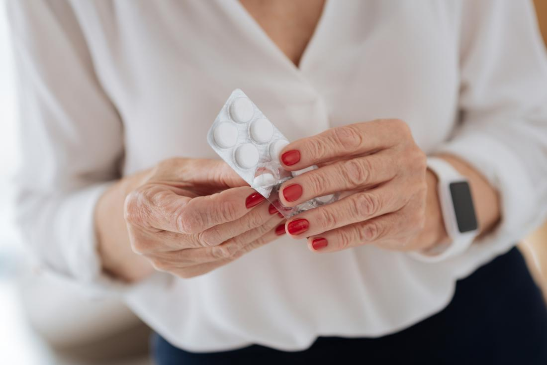 Woman taking neurobion supplement pills out of blister pack