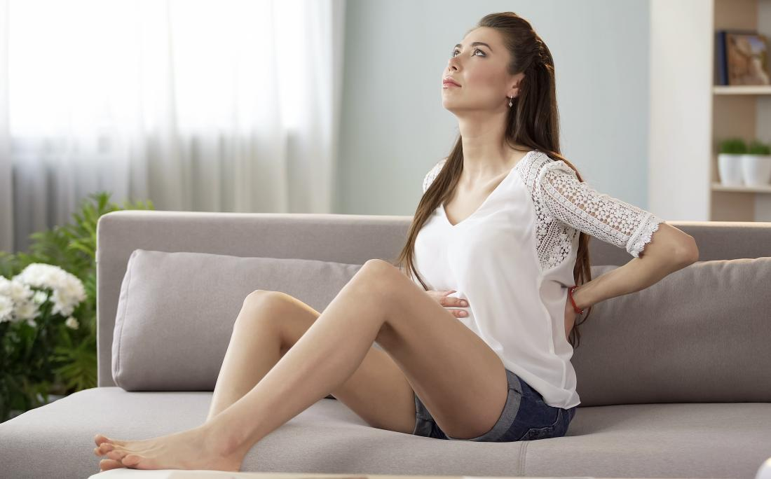 Pregnant woman sitting on sofa experience back and rib pain.