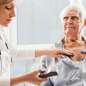 A nurse performs an EKG exam on a senior patient.