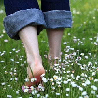 A woman walks barefoot through the grass.