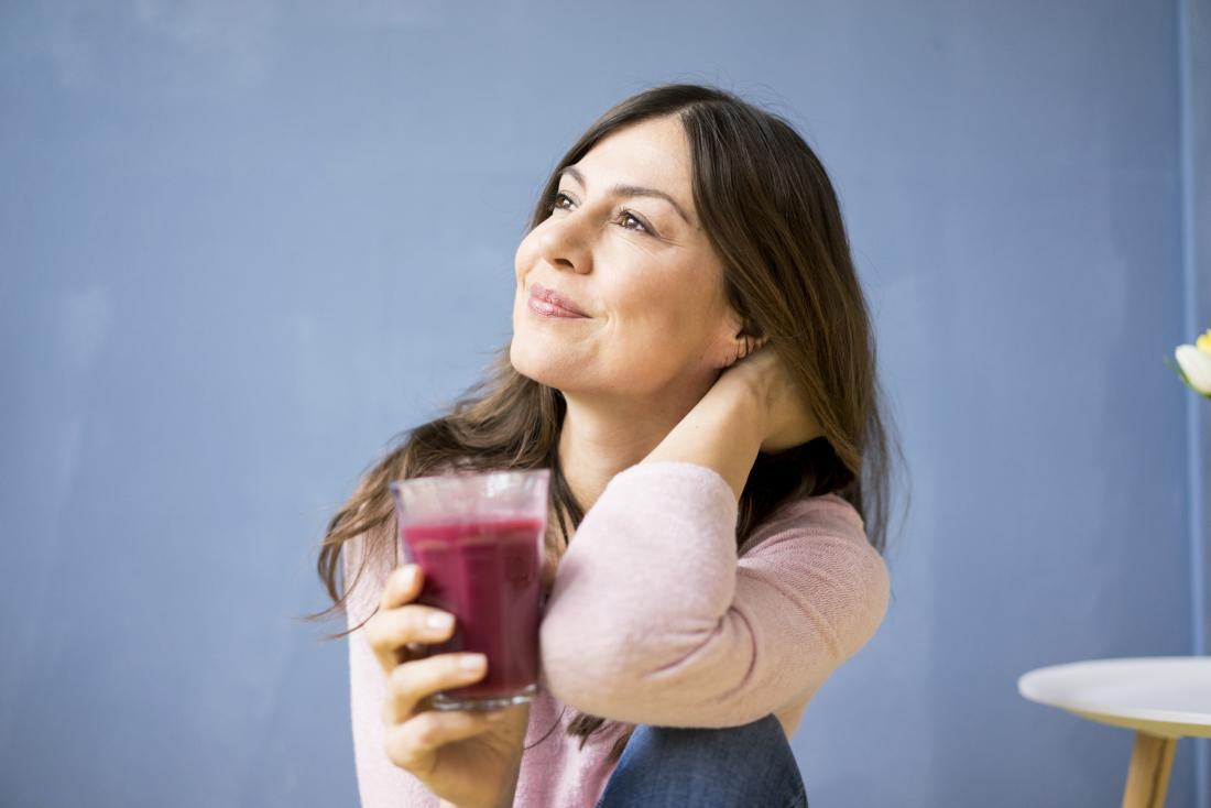 woman drinking a glass of red juice