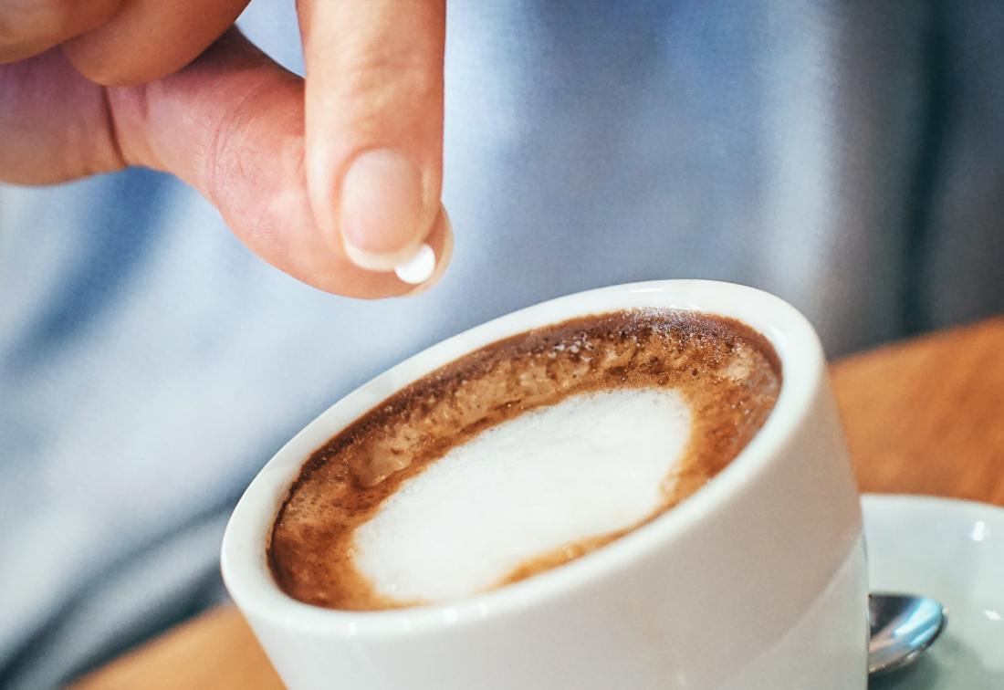 person using aspartame to sweeten coffee