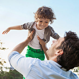 A man spins his son in the air playfully.