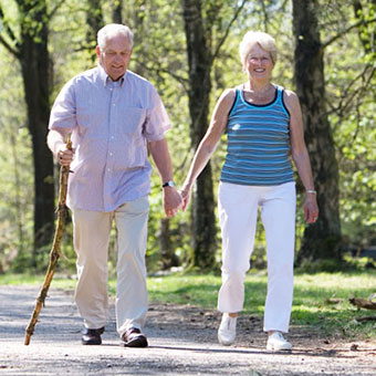 An elderly couple walks through the park.