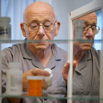 An elderly man taking his kidney medication from the medicine cabinet.