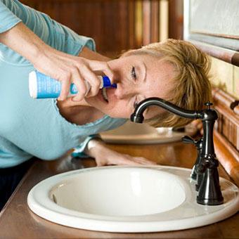 A woman using a sinus rinse kit.