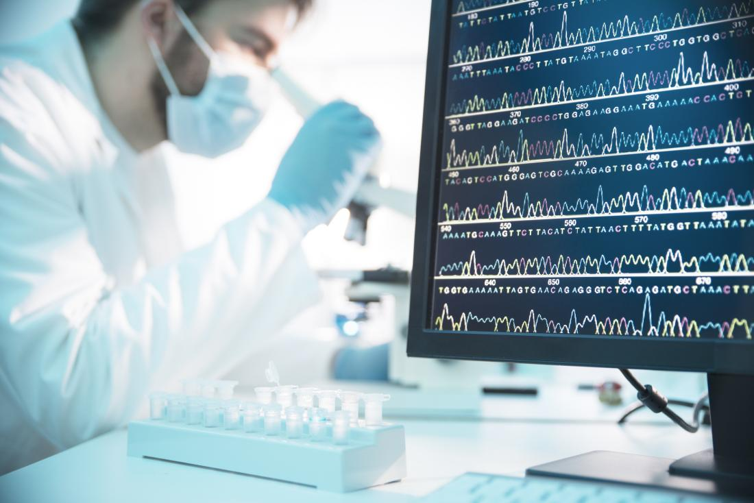 image of dna code on screen in foreground, scientists working in the background