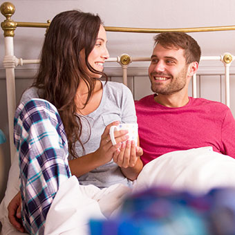 A couple having a discussion in bed.