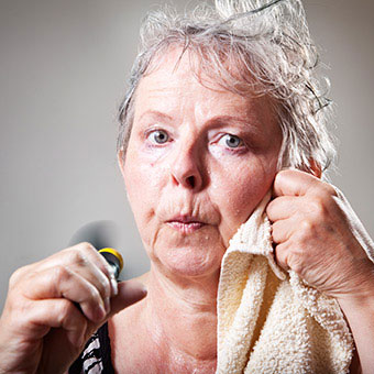 A older woman sweating from hot flashes holds a fan to her face.