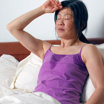 A woman in bed sweating.