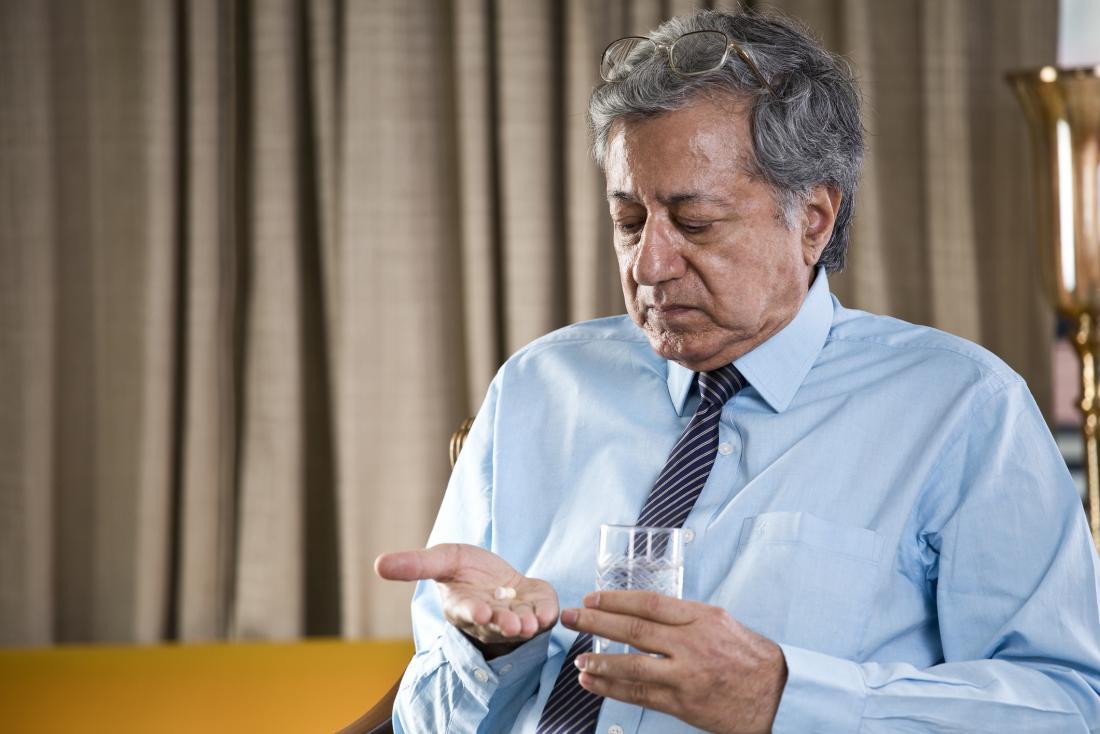 older man taking a pill