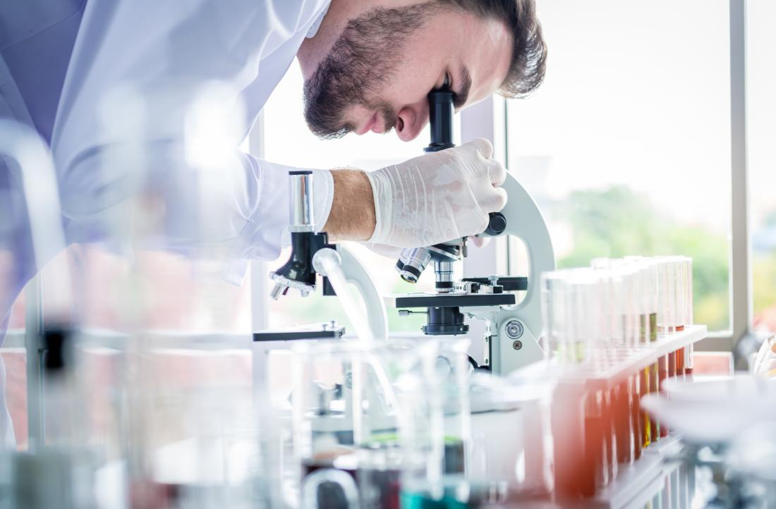 scientist looking at something through a microscope