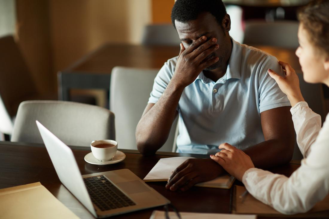 man looking stressed at work, being consoled
