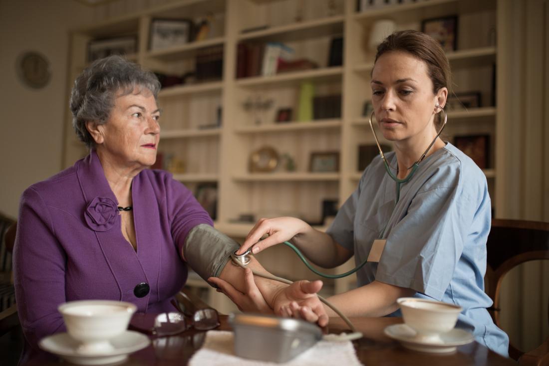 nurse checking patient blood pressure