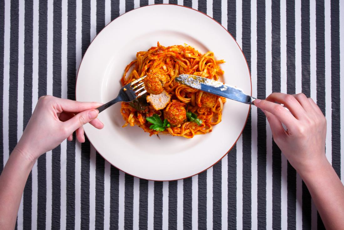close up of hands eating spaghetti with meatballs