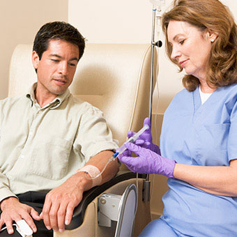 A nurse gives a patient IV treatment for multiple sclerosis.