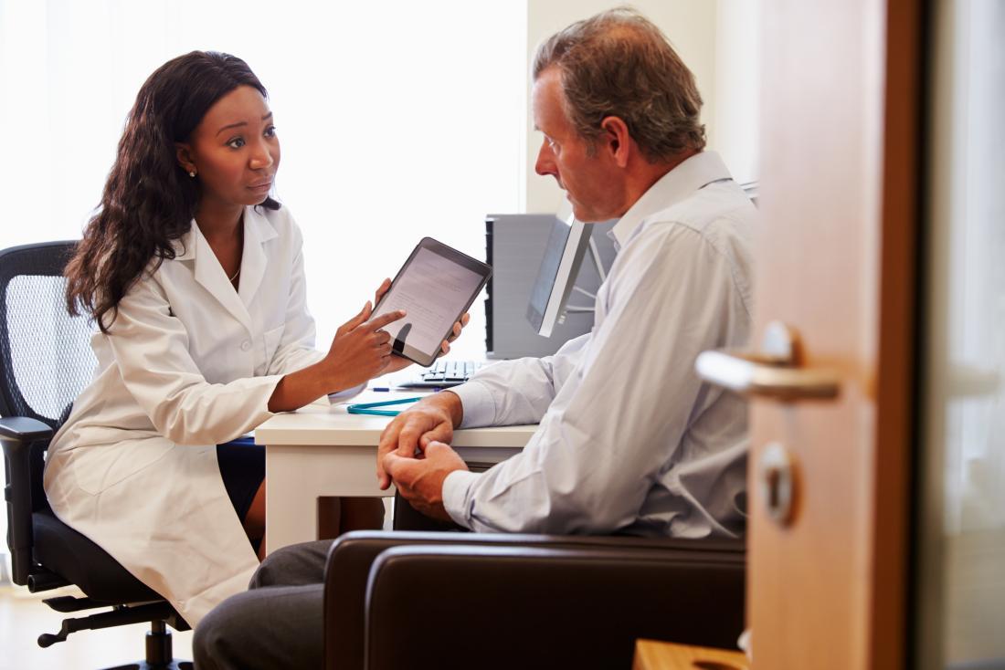 healthcare professional explaining something to senior man patient