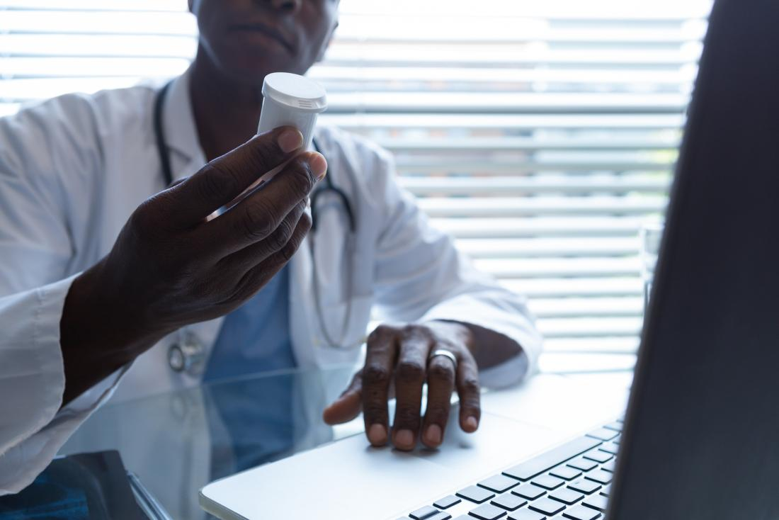 doctor looking at bottle of medication closely