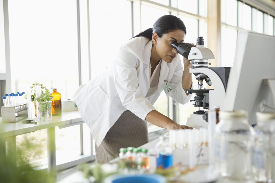 researcher peering into microscope
