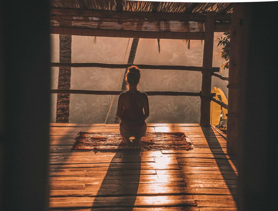 person meditating at sunset