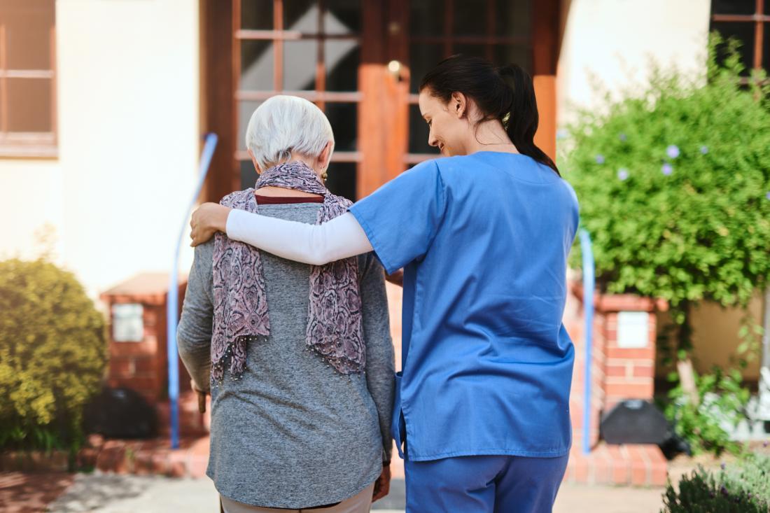 senior walking with nurse seen from behind