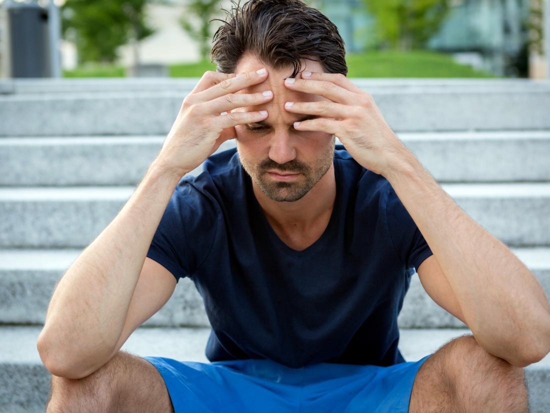 a man sat on some steps with a headache because he has Aplastic anemia
