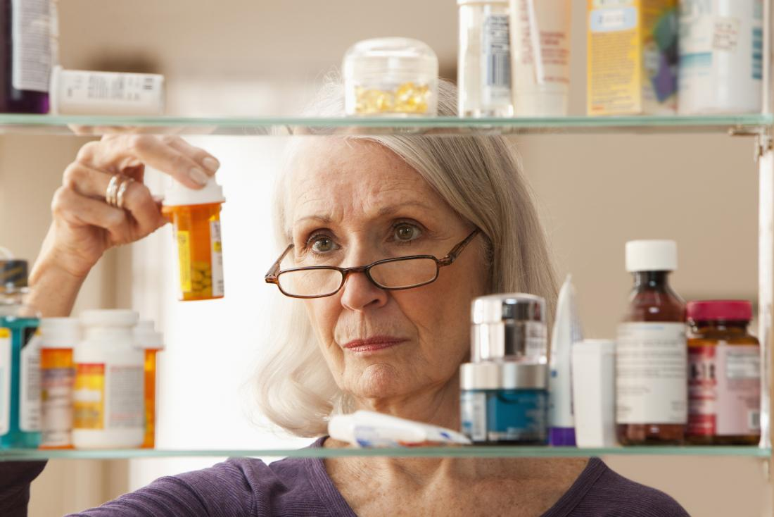 older woman lifting a pill container
