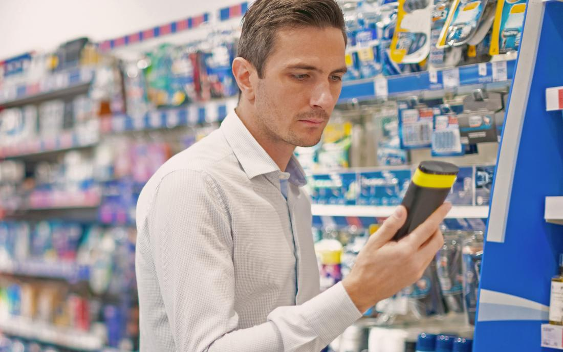 a man checking to see if there any sulfates in a shampoo he's buying.