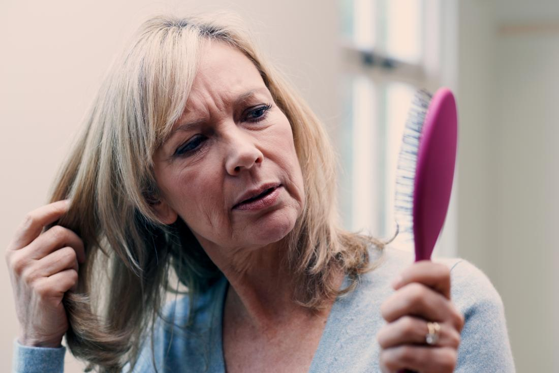 a woman looking at a hair brush and wondering if saw palmetto might help stop her hair from falling out