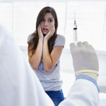 A woman afraid at the sight of the needle injection she is about to receive.