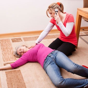 A woman calls 9-1-1 emergency to help a woman who that has fainted.