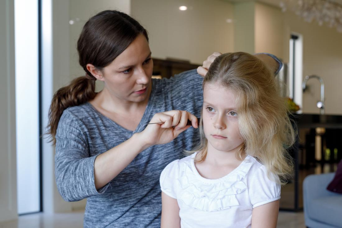 a parent or caregiver inspecting her child for hair loss.