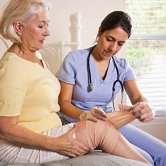 An at-home nurse caregiver wraps a woman's leg wound with a bandage.