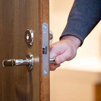 A man opens a door using the door handle. MRSA transmission can occur with objects such as door handles, floors, sinks, or towels that have been touched by a MRSA-infected person or carrier.