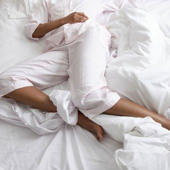 A woman in bed with restless leg syndrome (RLS).