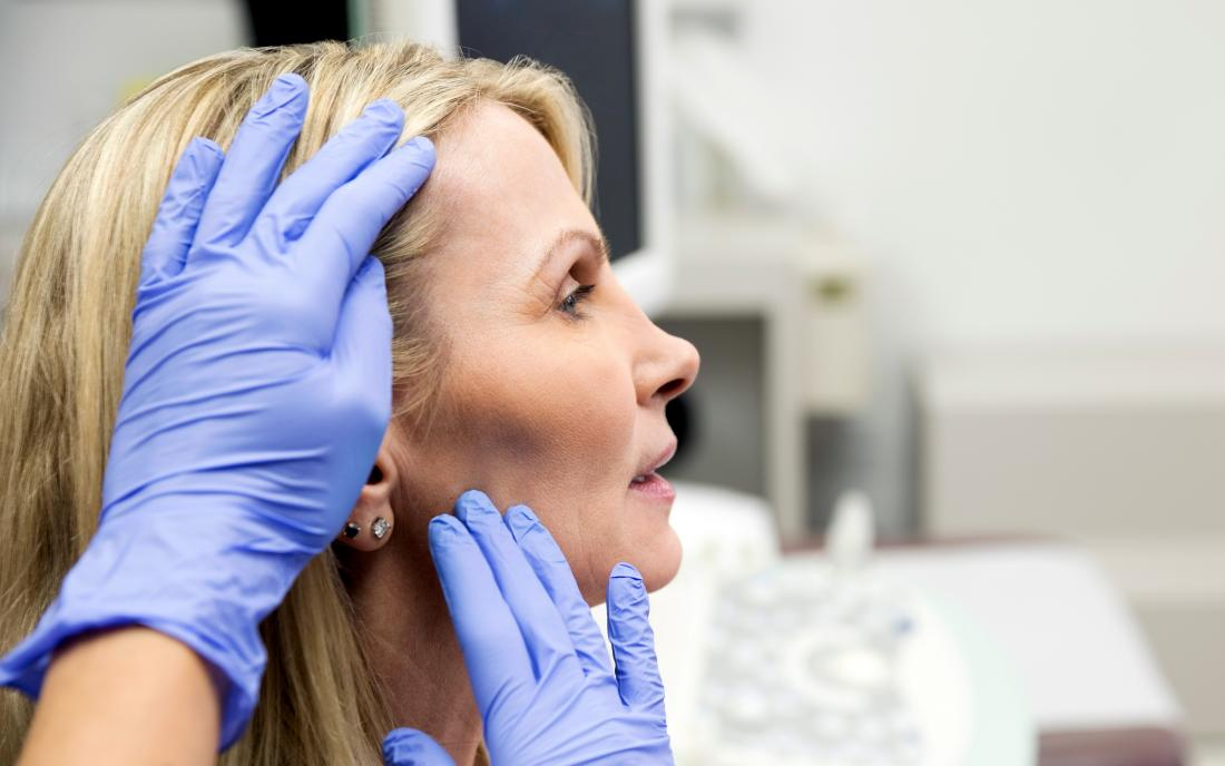 a doctor inspecting a dent in a womans head